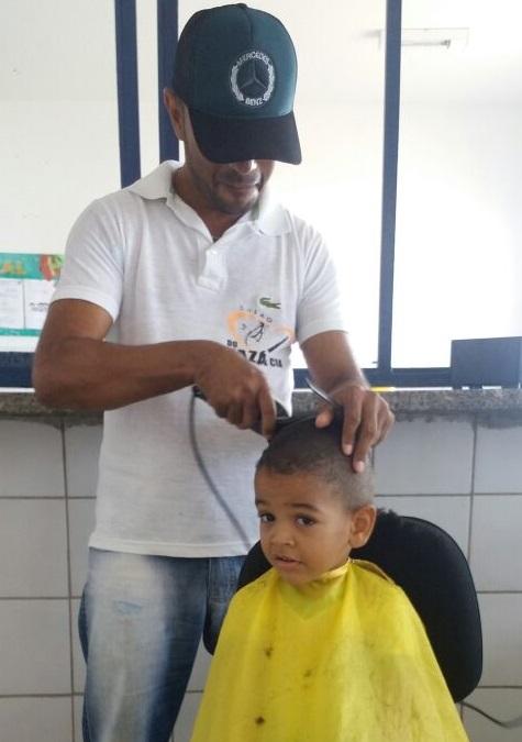 Zaza realiza corte de cabelo em aluno da creche