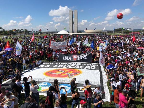 Cartaz Lula livre e camisas vermelhas mostram o tom politico